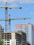 High-rise buildings under construction in progress. Construction cranes and unfinished building under a blue cloudy sky Stock Photo