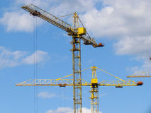 High-rise buildings under construction in progress. Construction cranes and unfinished building under a blue cloudy sky Royalty Free Stock Photos