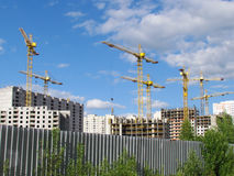 High-rise buildings under construction in progress. Construction cranes and unfinished building under a blue cloudy sky Royalty Free Stock Image