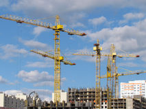 High-rise buildings under construction in progress. Construction cranes and unfinished building under a blue cloudy sky Royalty Free Stock Photo