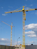High-rise buildings under construction in progress. Construction cranes and unfinished building under a blue cloudy sky Stock Photos