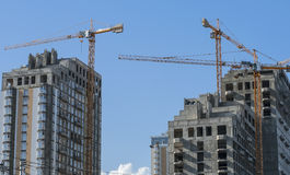 High-rise buildings in various stages of completion. Three monolithic construction house and three adjacent tower crane Stock Images
