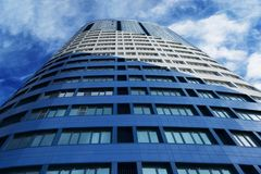 High-rise business center building at close range. Against a blue sky background Stock Photos