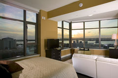 High Rise Condo. Interior of a High Rise Condo at Sunset with a bed and couch in the foreground Royalty Free Stock Photos