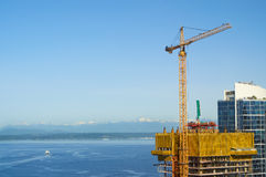 High-rise construction crane with ferry boat Royalty Free Stock Images