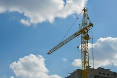 High-rise construction crane with a long arrow of yellow color against the blue sky over a new multi-storey building of concrete royalty free stock photos