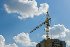 High-rise construction crane with a long arrow of yellow color against the blue sky over a new multi-storey building of concrete stock image