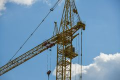 High-rise construction crane with a long arrow of yellow color against the blue sky over a new multi-storey building of concrete stock photos