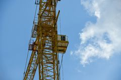 High-rise construction crane with a long arrow of yellow color against the blue sky over a new multi-storey building of concrete stock images