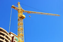 High-rise construction crane near the house. Royalty Free Stock Image