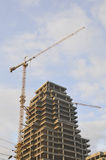 High rise construction site. With crane against a bright blue sky Stock Images