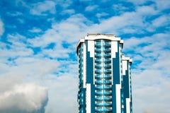 High-rise de bouw met een glasvoorgevel tegen een heldere blauwe hemel met voorgestelde wolken Royalty-vrije Stock Foto's