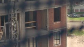 High-rise de bouwers werken in een opgeschorte wieg aan een voorgevel van de bouw Close-up stock video