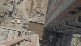 High-rise de bouwers werken in een opgeschorte wieg aan een voorgevel van de bouw close-up, mening van dak stock footage