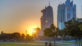 The high-rise district of Doha timelapse at sunset. Seen from the Hotel Park, with green lawn and artificial hill in the foreground. Skyscrapers and palms stock footage
