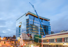 High-rise glass building under construction. The site with crane against evening sky Royalty Free Stock Image