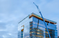 High-rise glass building under construction. The site with crane against evening sky Royalty Free Stock Photo