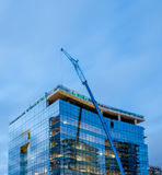 High-rise glass building under construction. The site with crane against evening sky Stock Image