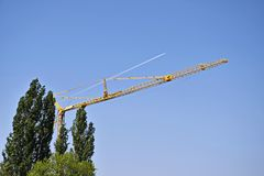 High-rise industrial crane against blue sky and green trees. stock photo