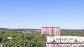 High-rise residential building among green trees. At summer day. Zoom lens stock video footage