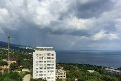 High-rise residential building in the low-rise resort village of Alupka. Rainbow over the sea on a cloudy day royalty free stock photography