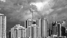 High rise tower crane and new residential buildings front view. Urban development theme. Sky and cloud background Stock Image