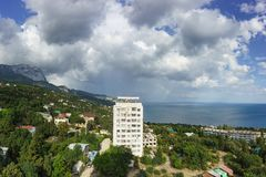 High-rise white house in the low-rise resort village of Alupka. Rainbow over the sea on a cloudy day royalty free stock photography