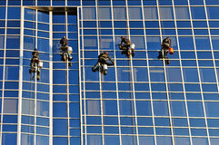 High rise window washers. Hanging from a building Royalty Free Stock Photos