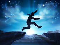 High Risk Business Concept. Businessman in silhouette in mid air jumping across a mountain gap. A concept for taking a leap of faith, being courageous or taking Stock Photo