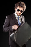 High risk businessman. Businessman wearing a suit with a secure suitcase attached with handcuffs royalty free stock photo