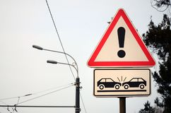 High risk of collision. A road sign with an exclamation point an. D two cars that crashed into each other royalty free stock photos