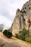 High rock. High craggy rock in cloudy day stock photos