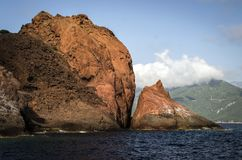 High rock formations above the blue sea covered by trees on the coast. Of Corsica Stock Image