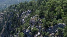 High rocky cliff, flowing into the Mediterranean Sea. Panoramic view. Couple of tourists. Aerial photography stock footage