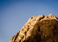 High rocky mountain against a blue sky. High rocky mountain against a clear blue sky royalty free stock photography
