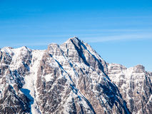 High rocky snowy peak on sunny winter day with blue sky. Alpine mountain ridge Royalty Free Stock Photos
