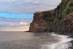 High rugged rocky coastline against cloudy sky at sunset. This photo was taken from sandy beach Praia da Calheta, Madeira island stock image