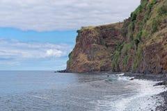 High rugged rocky coastline in Calheta. Madeira island, Portugal. High rugged rocky coastline against cloudy sky in Calheta on Portuguese island of Madeira. This stock photo