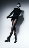 High scary woman in torn pantyhose. In studio Stock Image