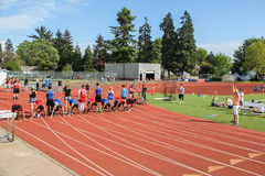 High school athletes set for 100 meter run. Corvallis, OR, April 20: High school racers leaving their blocks for a hundred meter race. Blocks supported by fellow stock photography