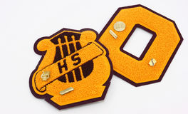 High School Awards. Gold and maroon colored high school letterman's awards, with pins, photographed on a white background. One is a music award with a band pin Stock Image