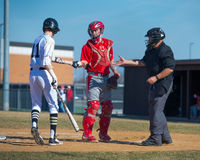 High School Baseball batter hands ball to catcher. Who will give it to the umpire Stock Photos