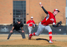 High School Baseball pitcher throws a pitch. While the 2nd baseman and umpire look on Stock Photography