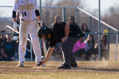 High school baseball umpire dusts off home plate. Before the right handed next batter bats Royalty Free Stock Images