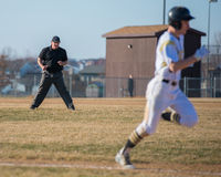 High school baseball umpire watches the runner. To first in order to make the call Stock Photography
