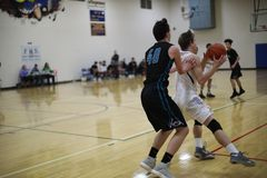 High school basketball game. Teenagers taking part in high school basketball game stock photography