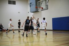 High school basketball. Players from two teams in the process of playing a game and making an attempt at a basket in a school gym royalty free stock photography