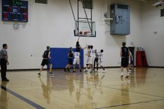 High school basketball teams in action. Two high school teams playing in basketball game stock photo
