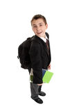 High School boy carrying bag and books. High school student (pre teen) carrying school bag backpack and text books.  He is in uniform, standing sideways and Stock Images