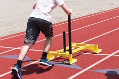 High school boy pushing a sled on a track Royalty Free Stock Photo
